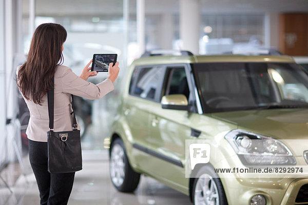 Mittlere erwachsene Frau beim Fotografieren des Autos im Ausstellungsraum