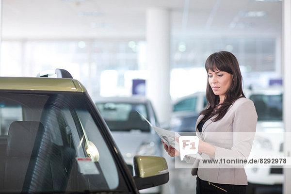 Mittlere erwachsene Frau  die im Ausstellungsraum eine Broschüre über das Auto checkt.