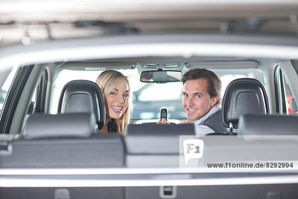 Paar sitzend im neuen Auto im Showroom