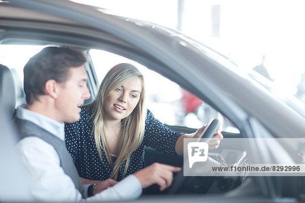 Autoverkäufer berät junge Frau im Autohaus