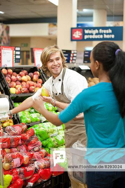 Junge männliche Verkäuferin bei der Auswahl der Äpfel für den Kunden