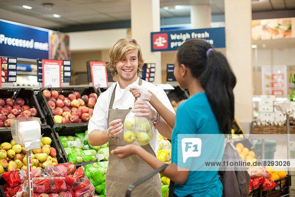 Junge männliche Verkäuferin bei der Übergabe von Äpfeln an den Kunden