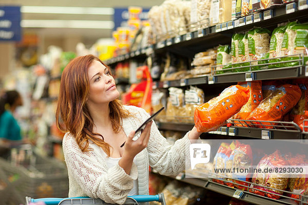Shopperin mit digitalem Tablett im Supermarkt
