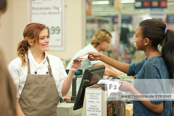 Verkäuferin bei der Übergabe der Rechnung an den Kunden