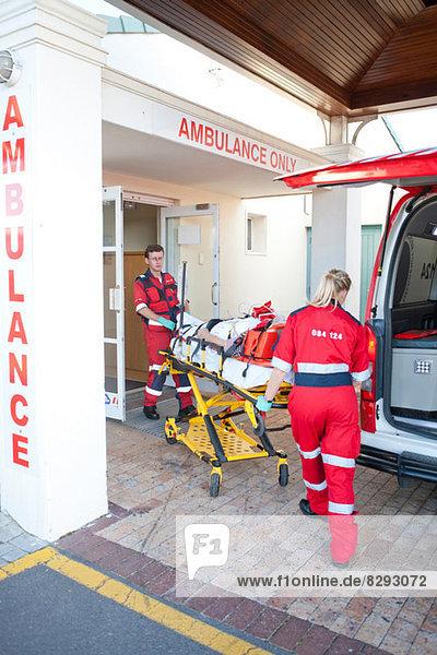 Rettungssanitäter bewegen den Patienten durch die Tür des Krankenhauses