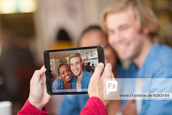 Gruppe von Freunden im Café fotografieren mit digitalem Tablett