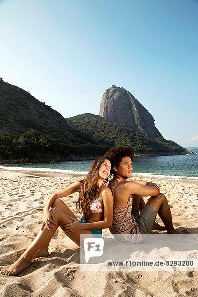 Couple relaxing on beach  Rio de Janeiro  Brazil