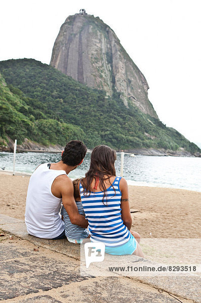 Family sitting on wall looking at Sugarloaf Mountain  Rio de Janeiro  Brazil