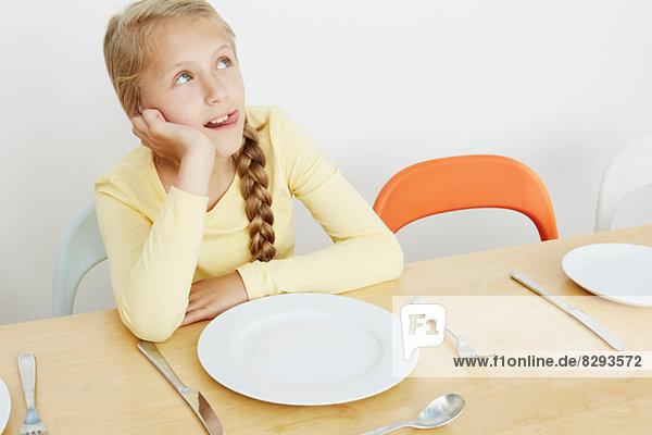Mädchen am Tisch sitzend mit leerem Teller  aufblickend