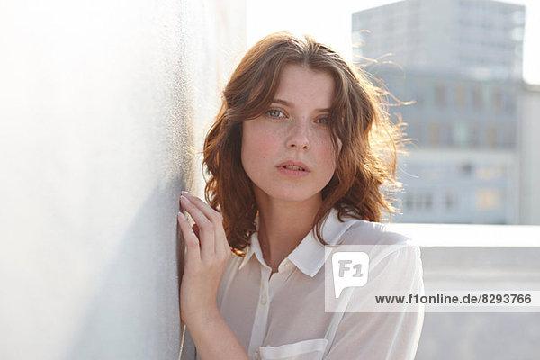 Porträt einer jungen Frau  die sich an die Wand lehnt