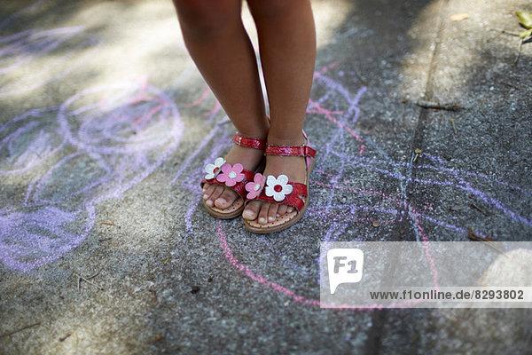 Mädchenbeine auf Kreidezeichnung stehend