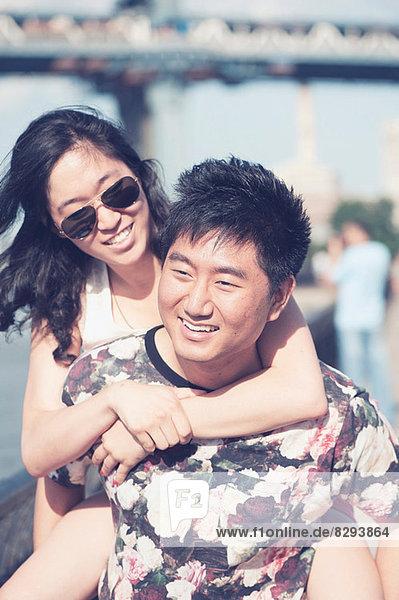 Junger Mann beim Huckepackfahren mit Freundin