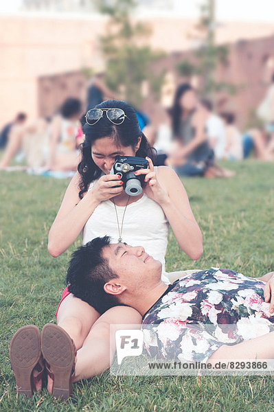 Young woman taking photograph of boyfriend