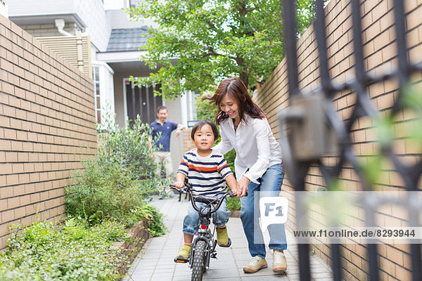 Mutter hilft dem Sohn beim Radfahren