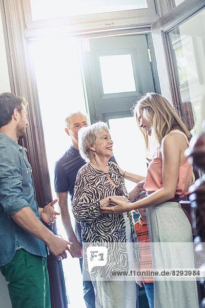 Frau begrüßt Eltern im Flur Frau begrüßt Eltern im Flur