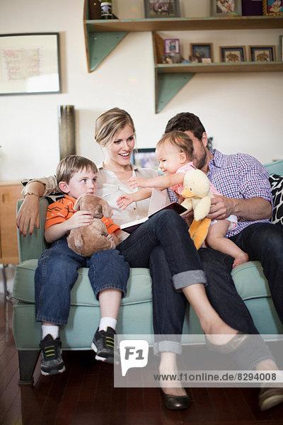 Eltern mit zwei Kindern sitzen auf dem Sofa Eltern mit zwei Kindern sitzen auf dem Sofa