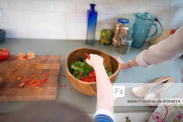 Mutter und Sohn bereiten Salat auf der Küchentheke zu. Mutter und Sohn bereiten Salat auf der Küchentheke zu.