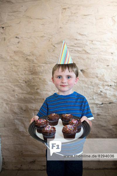 Porträt des Jungen mit Partyhut und Muffins Porträt des Jungen mit Partyhut und Muffins