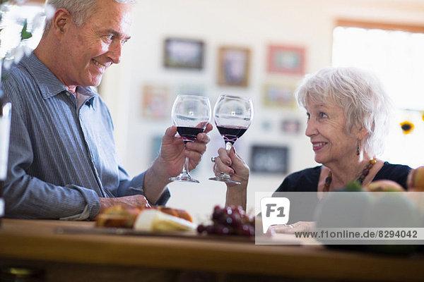 Seniorenpaar-Toasting mit Rotwein