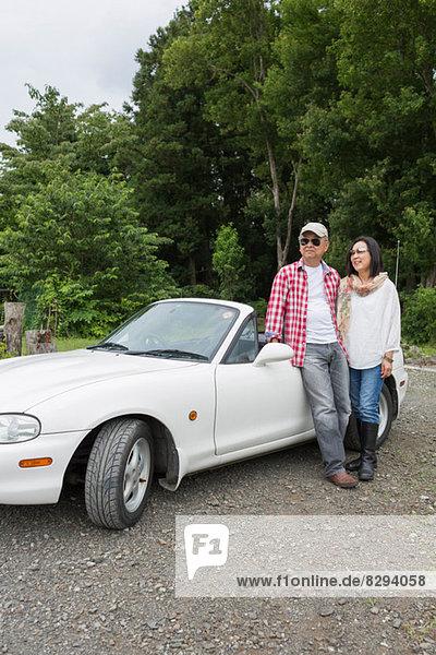 Paar steht neben dem Auto