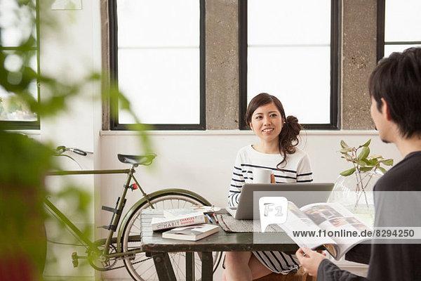 Junges Paar am Tisch sitzend mit Computer