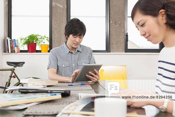 Junges Paar im Sitzen am Schreibtisch in der Wohnung