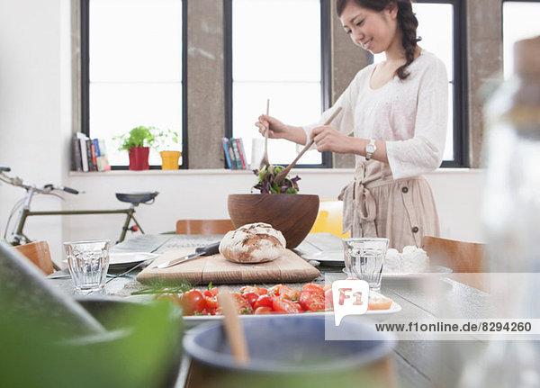 Junge Frau beim Zubereiten des Essens am Tisch