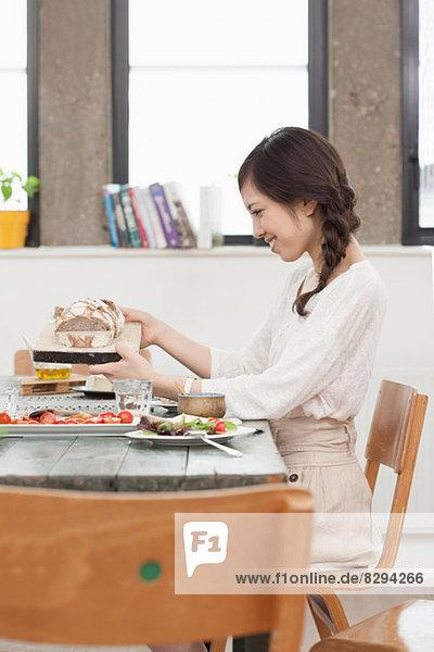 Junge Frau beim Mittagessen am Tisch