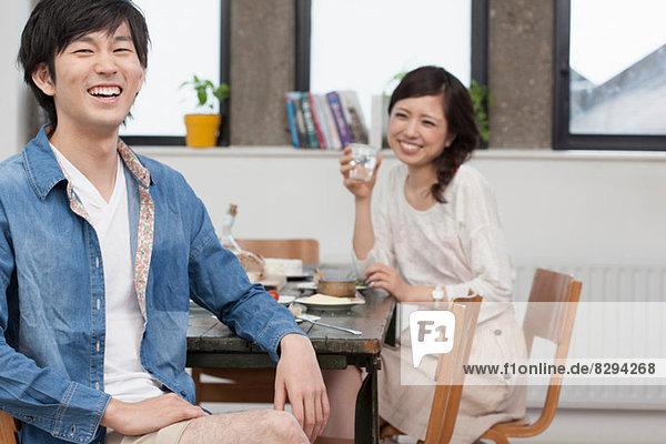 Porträt eines jungen Paares beim Essen am Tisch