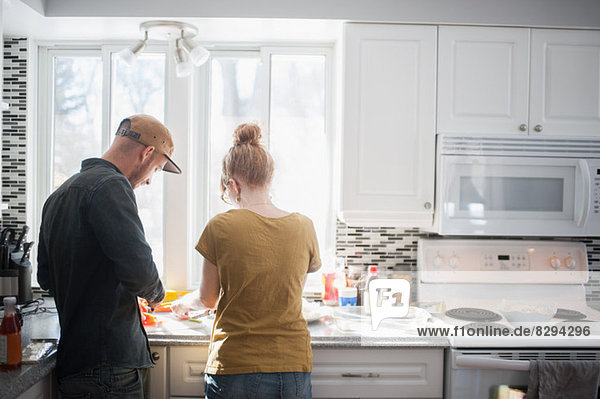 Mid adult couple preparing food in kitchen