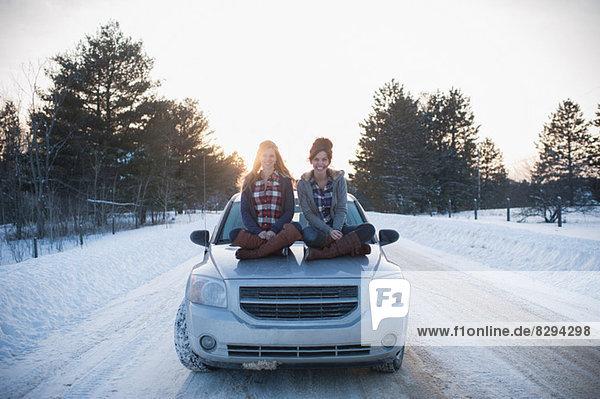 Zwei Frauen sitzen auf der Motorhaube im Schnee