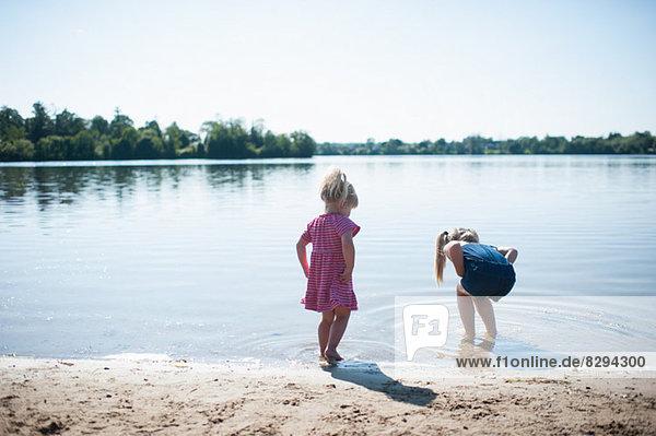 Two girls playing by lake
