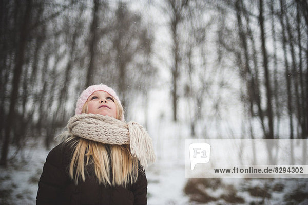 Girl wearing hat and scarf looking up in winter
