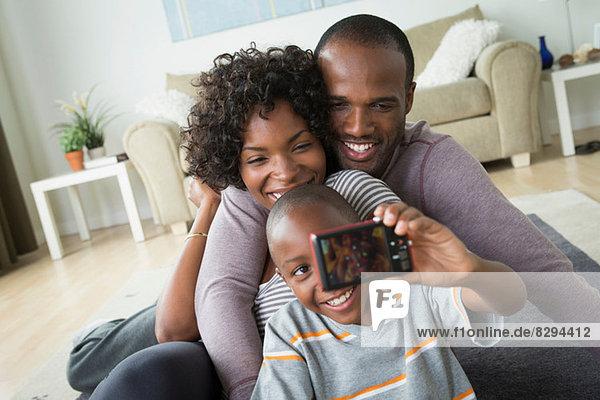 Eltern und Sohn fotografieren sich selbst mit Digitalkamera