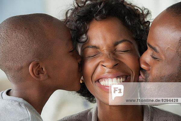 Junge und Mann küssen Frau auf Wangen