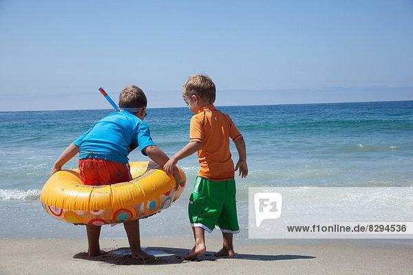 Zwei junge Brüder spielen mit Gummiring am Strand