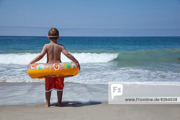 Junge spielt mit Gummiring am Strand