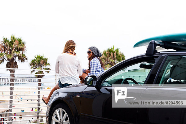 Female friends sitting on car  Hermosa Beach  California  USA