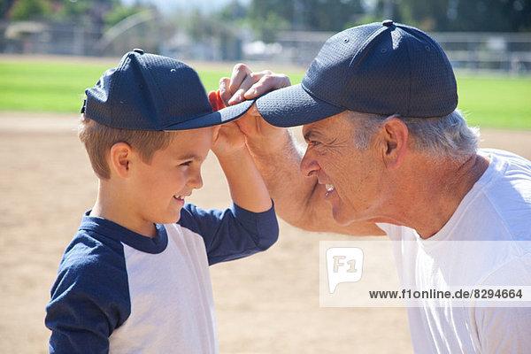 Junge und Großvater in Baseballkappen  von Angesicht zu Angesicht