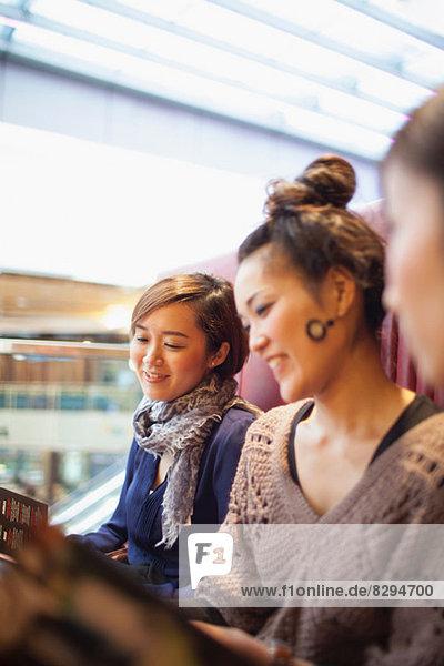 Junge Frauen lesen Menüs im Café