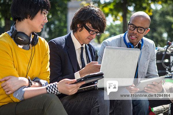 Drei gelegentliche Geschäftsleute mit Laptop im Park