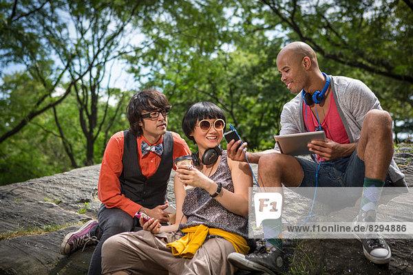 Drei Freunde sitzen auf Steinen mit mp3-Player und Tablett