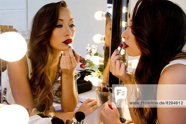 Frau mit Lippenstift im Spiegel