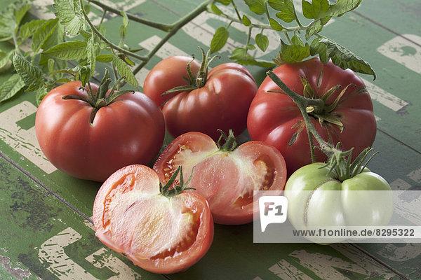 Whole and sliced Silesian raspberry tomatoes (Solanum lycopersicum)  studio shot