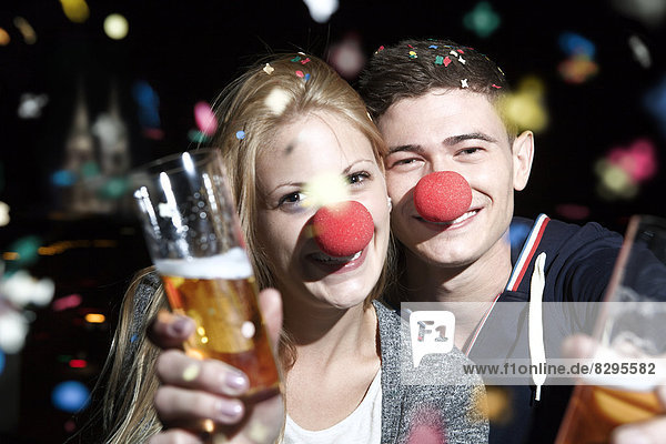 Germany  North Rhine Westphalia  Cologne  young couple with clowns noses toasting