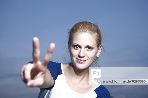 Young woman showing victory sign Young woman showing victory sign