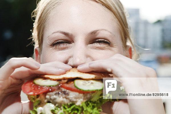 Junge Frau beim Essen eines Hamburgers