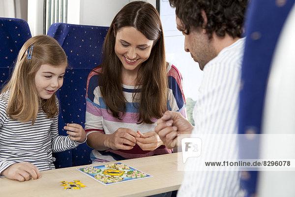 Glückliche Familie beim Spielen im Zug