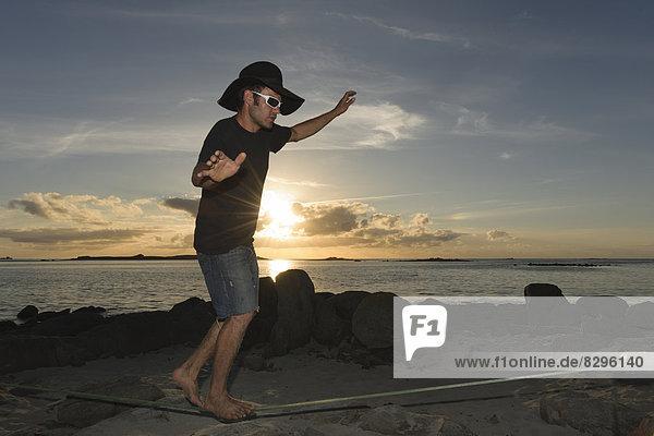 France  Bretagne  Landeda  Man balancing on slackline on beach