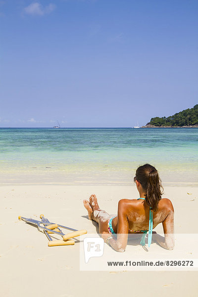 Thailand  Insel Koh Surin  Frau mit Krücken am weißen Sandstrand liegend